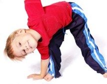 A cute four year old boy wearing red and blue bending over to touch his right toes.